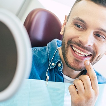 Male patient smiling at reflection at dentist's appointment
