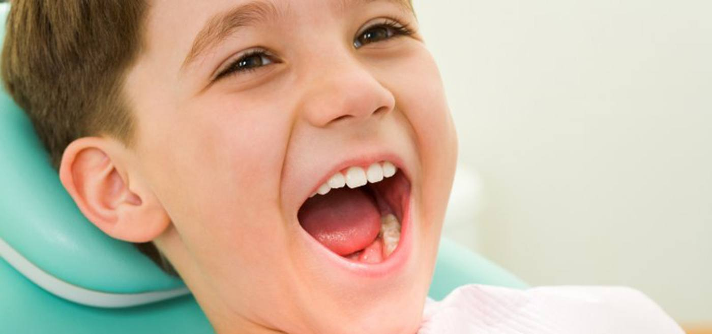 Young boy smiles after getting children's dental sealants in Allen