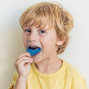 Little boy placing blue athletic mouthguard