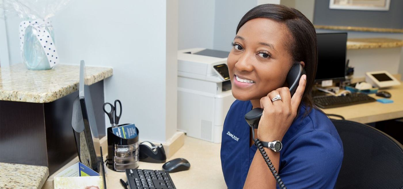 Smiling team member discussing dental insurance with patient on phone