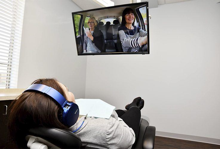 Relaxed dentistry patient watching TV in dental exam room