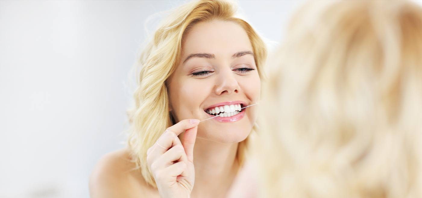 Woman flossing teeth to prevent gum disease