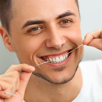 Man flossing teeth to prevent gum disease after antibiotic therapy