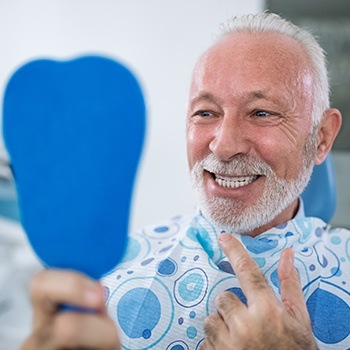 Older man looking at healthy smile thanks to periodontal maintenance