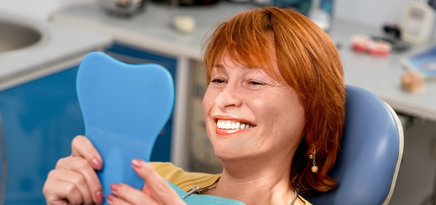 Older woman looking at smile after preventive dentistry visit