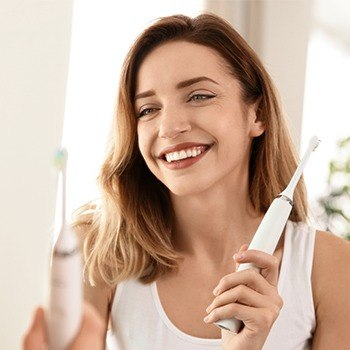 Smiling woman holding mechanical toothbrush after completing at-home oral hygiene routine