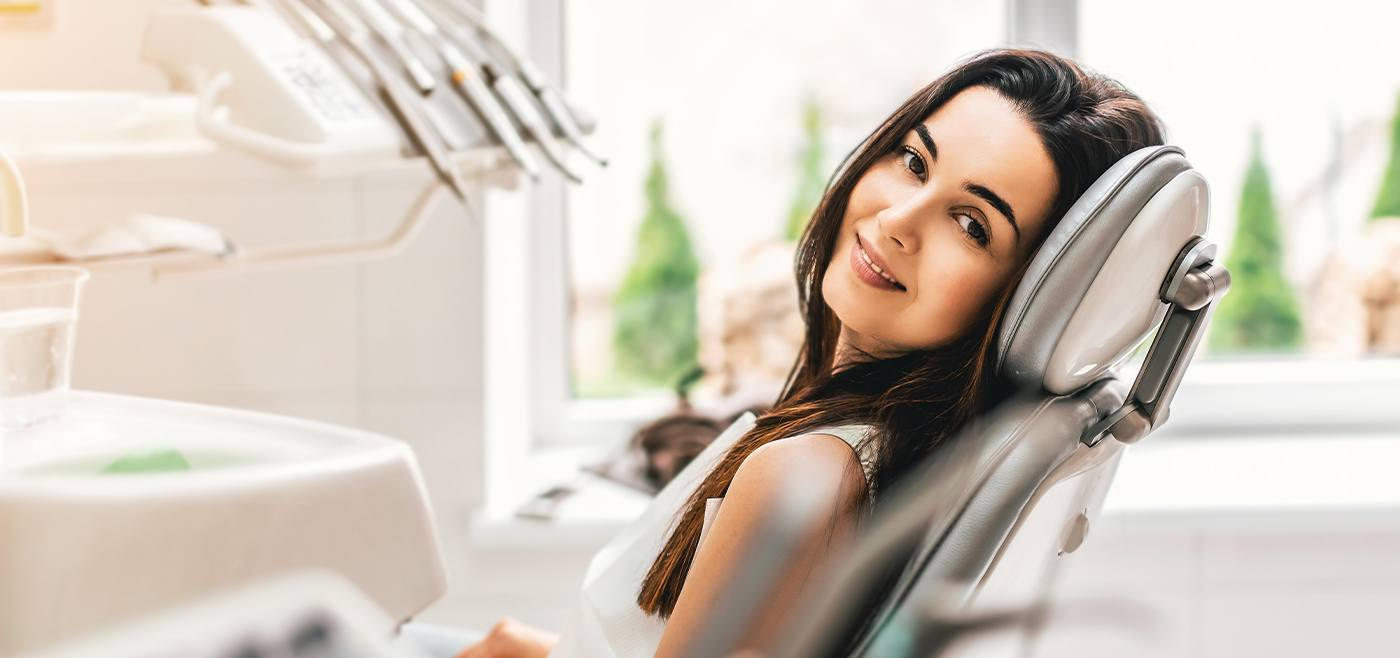 Woman in dental chair smiling after root canal therapy