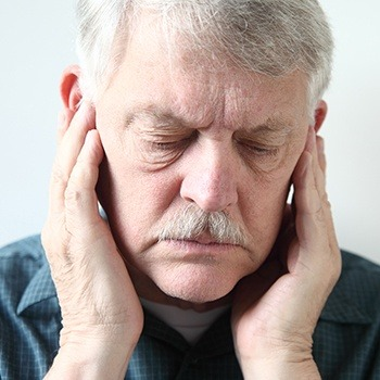 Older man with TMJ dysfunction holding jaw joints